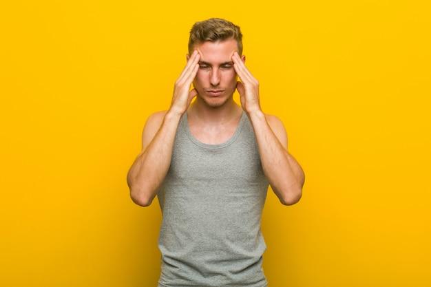 寺院に触れると頭痛を持つ若い白人スポーツ男。