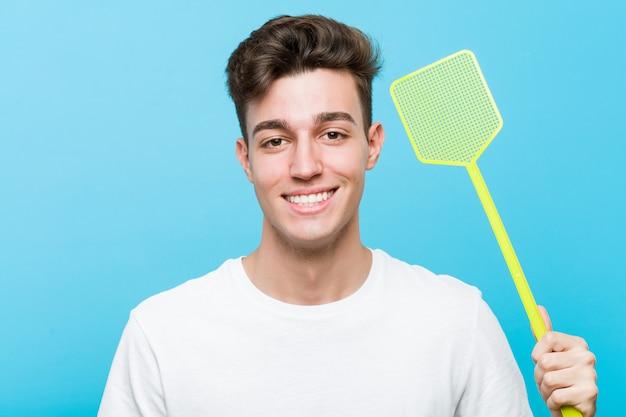 ハエたたきを保持している若い白人男は幸せ、笑顔、陽気です。
