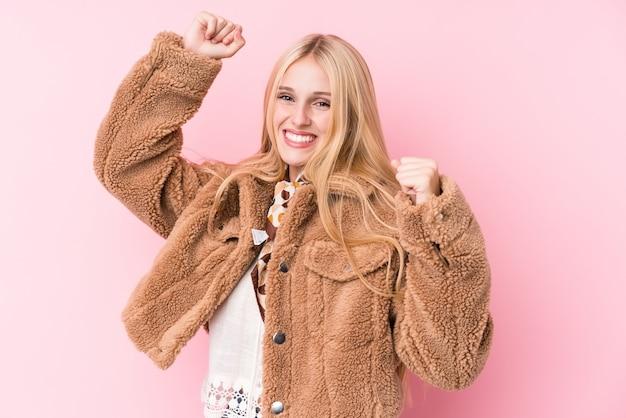 Молодая блондинка в пальто против розовой стены, празднование особого дня, прыжки и поднять руки с энергией.