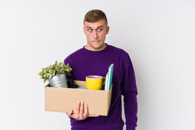 混乱している新しい家に引っ越す若い白人男性は、疑わしく不安を感じています。