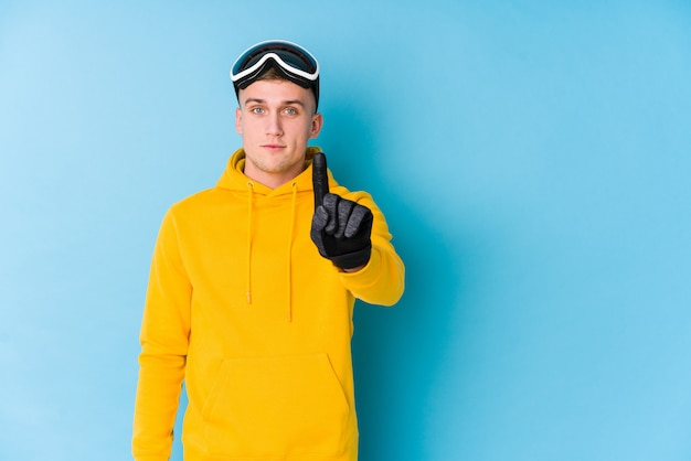 指でナンバーワンを示す若いスキーヤーの男。