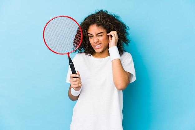 手で耳を覆うバドミントンを演奏若いアフリカ系アメリカ人女性。
