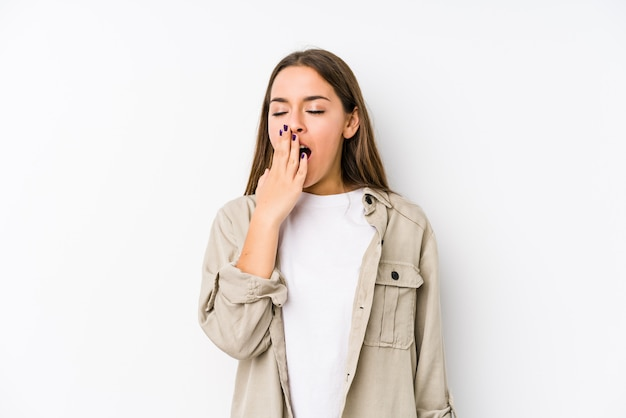 若い白人女性は、手で口を覆っている疲れたジェスチャーを示すあくびを分離しました。