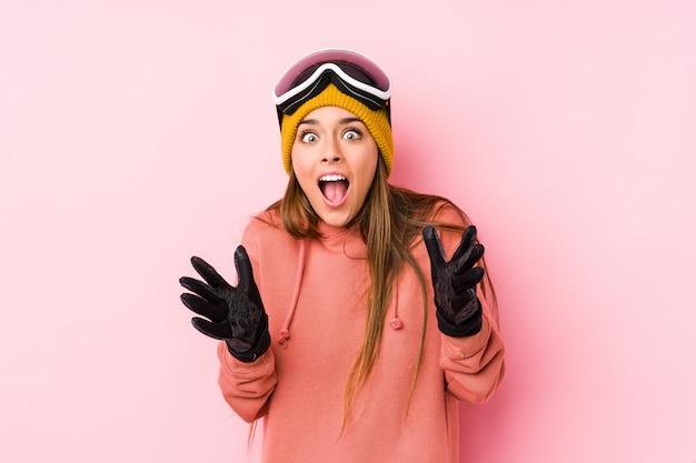 勝利または成功を祝って分離されたスキー服を着た若い白人女性は、彼は驚いてショックを受けた。