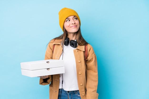 Молодая кавказская женщина держа пиццу изолировала мечтать достижения целей и задач