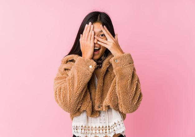 若いアジアの女性は、恐怖と緊張の指の間で点滅します。