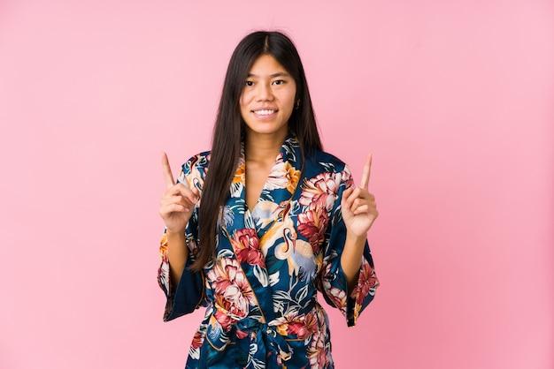 Молодая азиатская женщина нося пижамы кимоно показывает с обоими пальцами передней части вверх показывая пустое пространство.