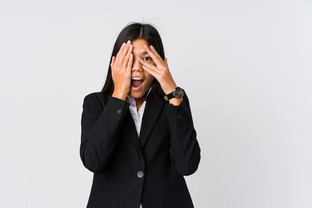 若いアジアビジネスの女性は、恐怖と緊張の指の間で点滅します。