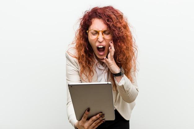 叫んでタブレットを保持している若い白人ビジネス赤毛の女性は前に興奮しています。