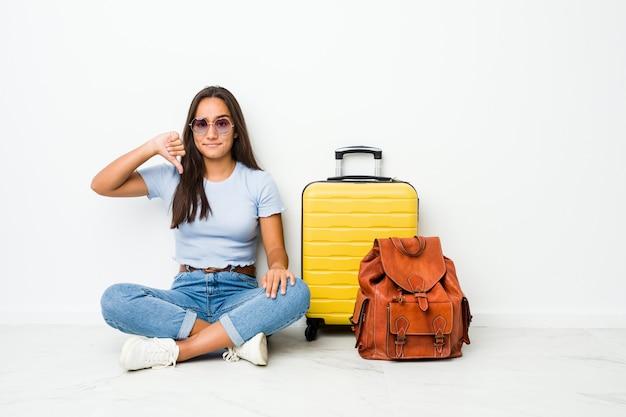 若い混合レースインドの女性が嫌いなジェスチャー、親指ダウンを示す旅行に行く準備ができています。