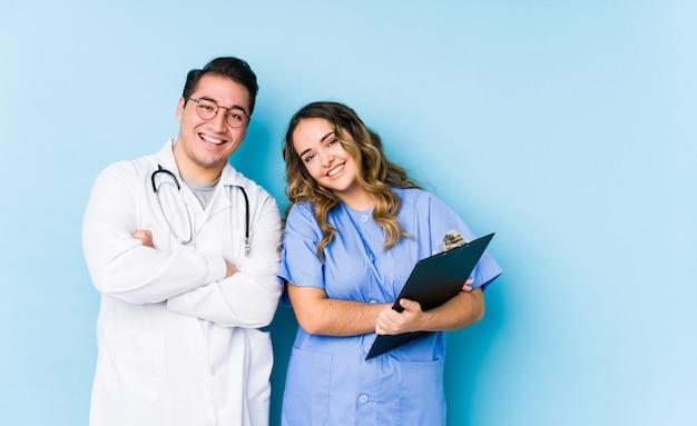 青い壁でポーズをとって若い医者カップルが笑って、楽しい時を過します。