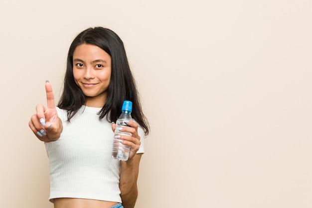 Молодая азиатская женщина держа показ бутылки одно с пальцем.