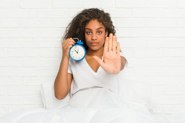 目覚まし時計を保持しているベッドに座っている若いアフリカ系アメリカ人女性は、差し出された手を示す一時停止の標識を防止します。