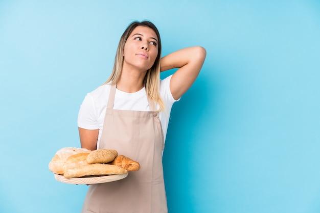 Молодая кавказская женщина хлебопека изолировала касаться задней части головы, думая и делая выбор.
