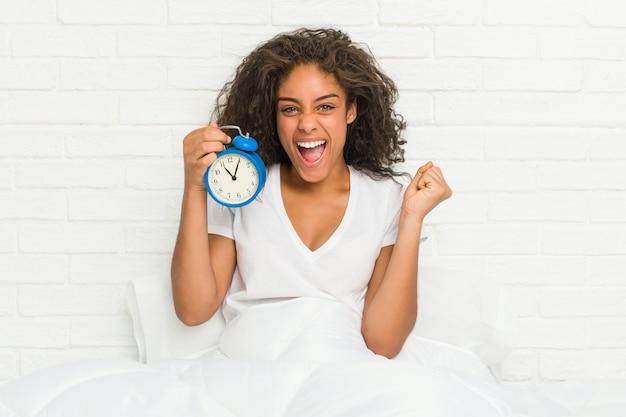 のんきで興奮して応援目覚まし時計を保持しているベッドに座っている若いアフリカ系アメリカ人女性。勝利のコンセプト。