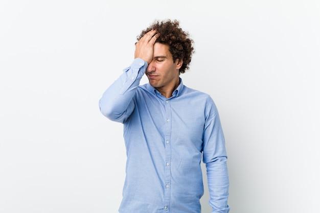 Молодой кудрявый зрелый человек, одетый в элегантную рубашку, забывая что-то, шлепая по лбу ладонью и закрывая глаза.