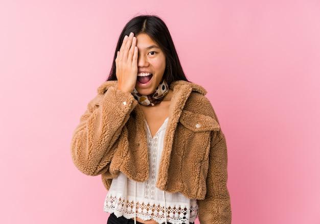 手のひらで顔の半分をカバーして楽しんで若いアジア女性。