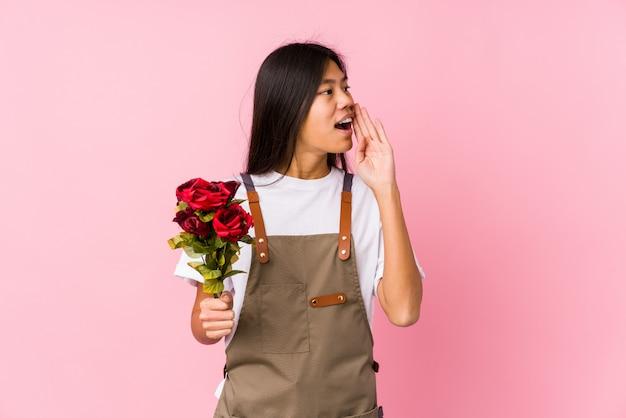 バラを保持している若い中国の庭師の女性は、叫び、開いた口の近くに手のひらを保持分離しました。