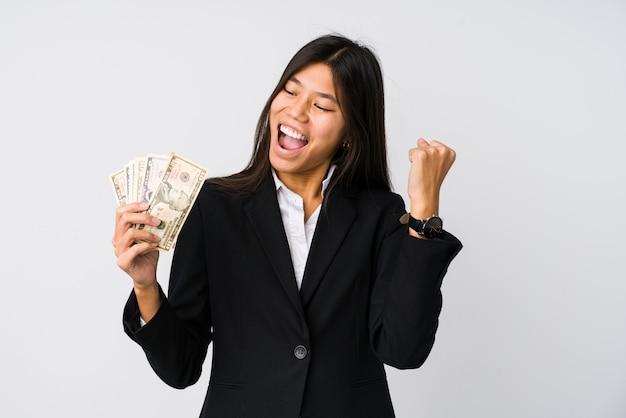 Молодая китайская бизнес-леди держа деньги изолированный