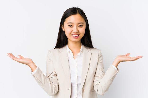 分離された若い中国のビジネス女性は腕でスケールになり、幸せと自信を感じています。