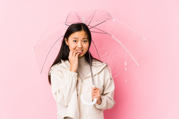 傘を保持している若い中国人女性は、痛烈な爪、神経質で非常に不安を分離しました。