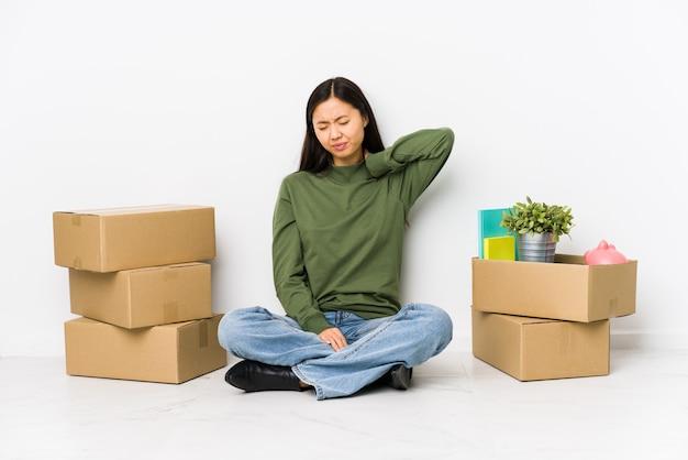 座りがちな生活のために首の痛みに苦しんでいる新しい家に移動する若い中国人女性。