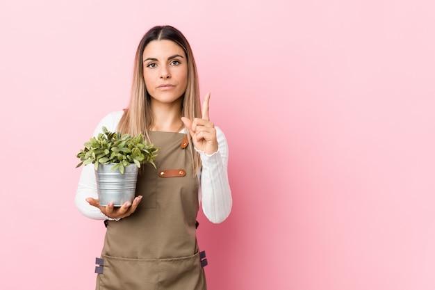 Молодая женщина садовника держа завод показывая номер один с пальцем.