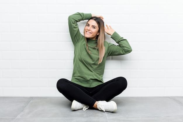リラックスした位置、腕を伸ばして床に座っている若い白人女性。