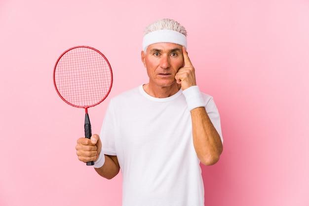 Человек постаретый серединой играя изолированный бадминтон указывая указывающ висок с пальцем, думая, сфокусированный на задаче.