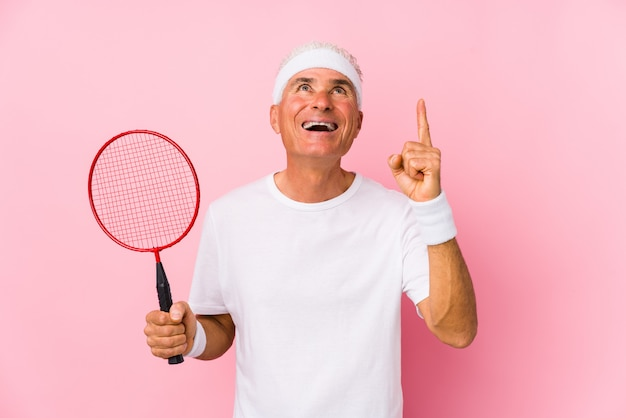 バドミントンをしている中年の男は、開いた口で逆さまを指しています。