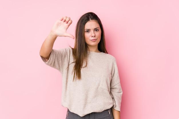若い白人女性が親指ダウン嫌いなジェスチャーを示す分離をポーズします。不一致の概念。