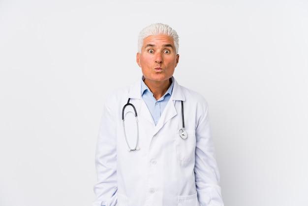 Зрелый кавказский доктор человек пожимает плечами плечи и смущенные открытые глаза.