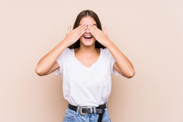孤立したポーズ若い白人女性は、手で目をカバーし、広く驚きを待っている笑顔。