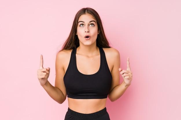 Молодая кавказская женщина фитнеса делая спорт изолировала указывать внешняя сторона с раскрытым ртом.