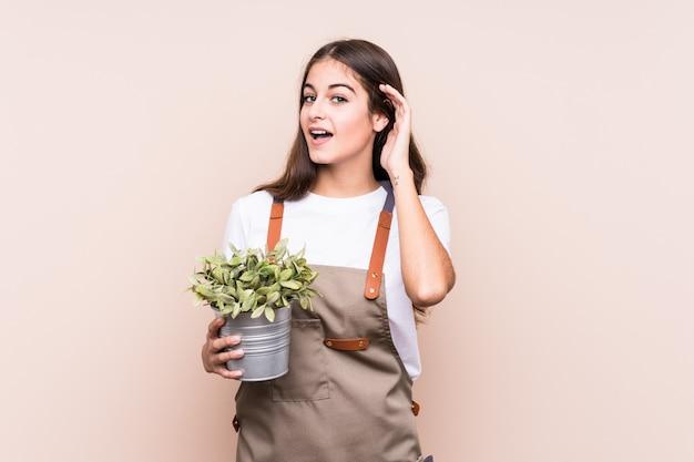 ゴシップを聞いて孤立した植物を保持している若い庭師白人女性。