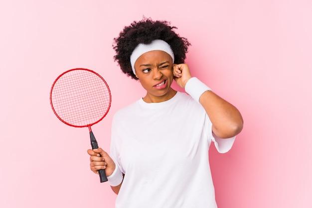 Молодая афро-американская женщина играя бадминтон изолировала покрывать уши руками.