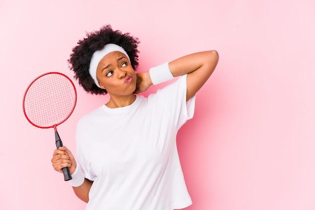 バドミントンをプレイ若いアフリカ系アメリカ人女性は、頭の後ろに触れる、考え、選択を分離しました。