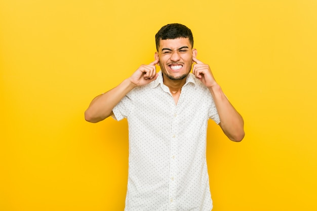 Молодой испанец человек, охватывающих уши руками.