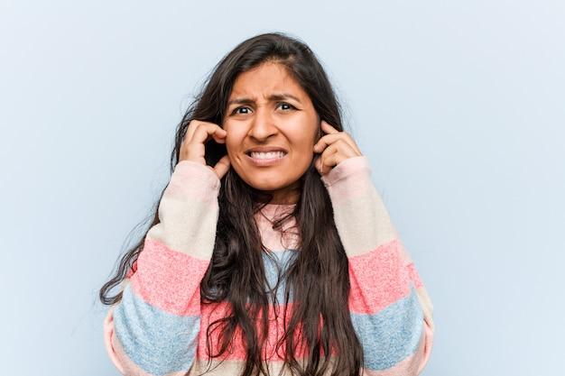 Молодые моды индийской женщины, охватывающих уши своими руками.
