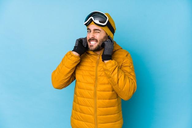 Молодой лыжник кавказских человек изолированы охватывающих уши руками.