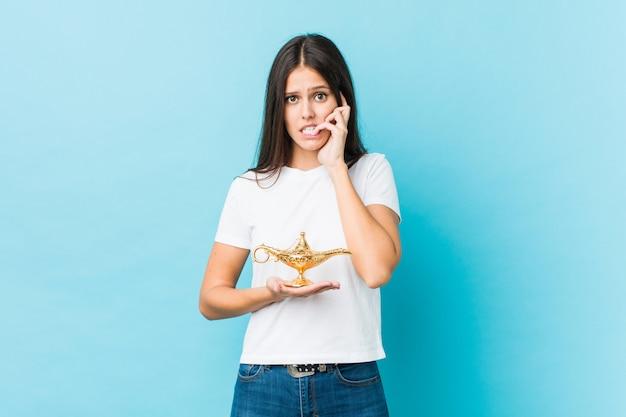 Молодая кавказская женщина держа волшебную лампу кусая ногти, нервная и очень тревожная.