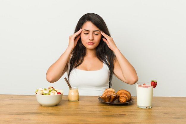 寺院に触れると頭痛を持っている朝食を取って若い曲線の女性。