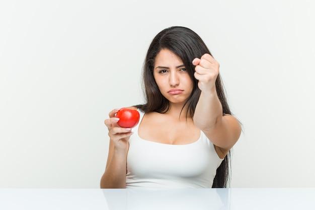 Молодая испанская женщина держа томат показывая кулак к с агрессивным выражением лица.