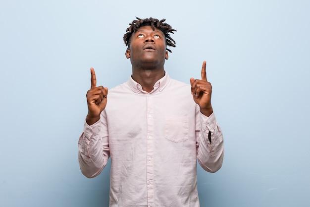 開いた口で逆さまを指している若いビジネスアフリカ黒人男性。