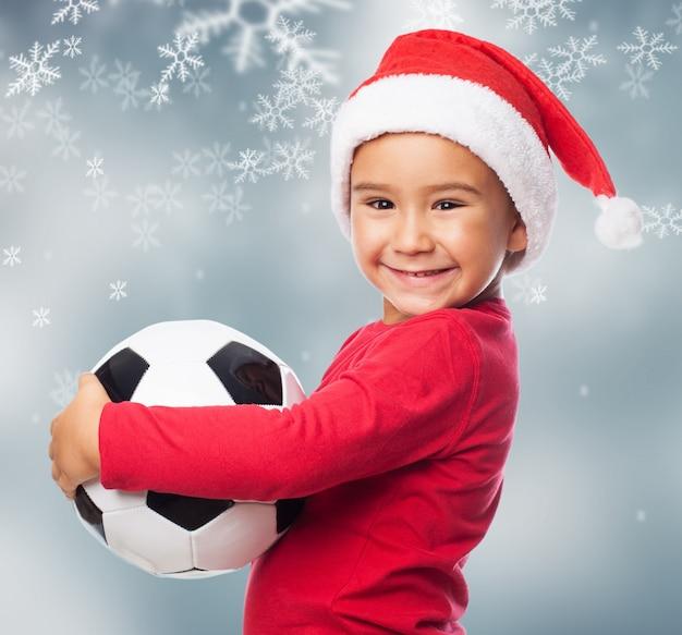 Радостный маленький мальчик, давая обнять его мяч
