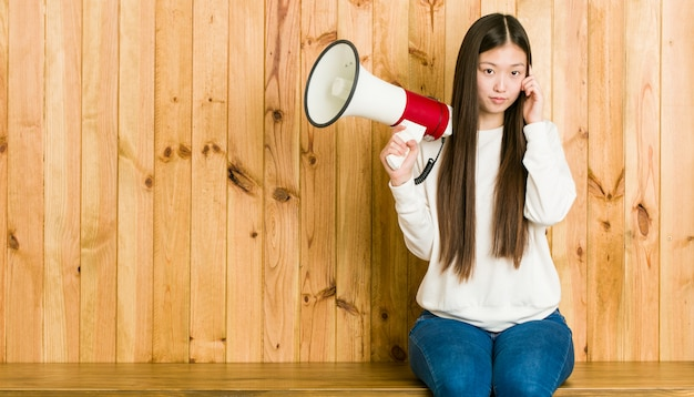 Молодая азиатская женщина держа мегафон указывая его висок с пальцем, думая, сфокусировала на задаче.