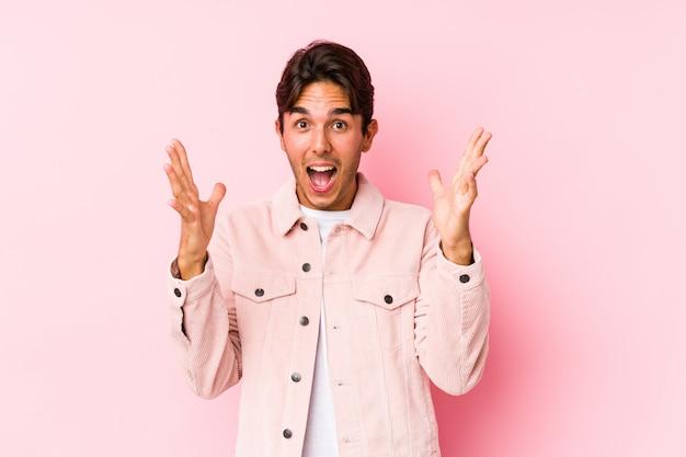 Молодой кавказский человек представляя в розовой изолированной стене празднующ победу или успех, он удивлен и потрясен.