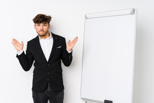 Молодой бизнес тренер арабского человека смущен и сомнительно пожимает плечами, чтобы держать копию пространства.
