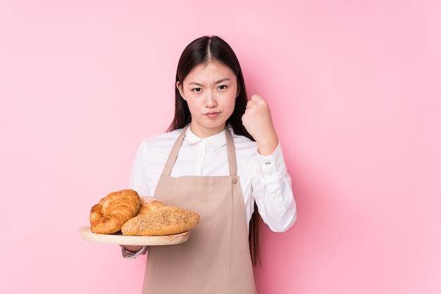 Молодая китайская женщина хлебопека изолировала показывать кулак к с агрессивным выражением лица.