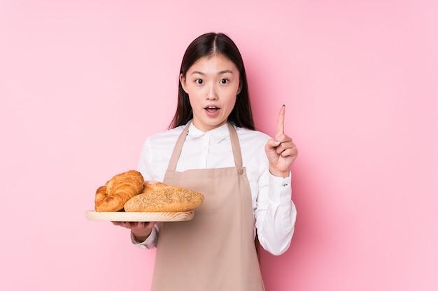 Молодая китайская женщина хлебопека изолировала иметь некоторую отличную идею, концепцию творческих способностей.